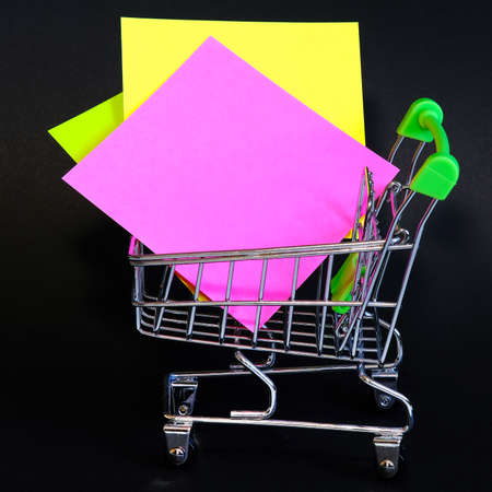 Colorful notes isolated on a black background. In the office basket.