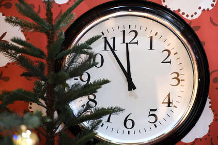 Beautiful expectation of the holiday. Watch with black hands on a white dial background. Happy start to the year