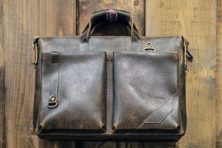 Leather backpacks and briefcases hang on the wall. The concept of stylish leather products. Bags, purses and belts
