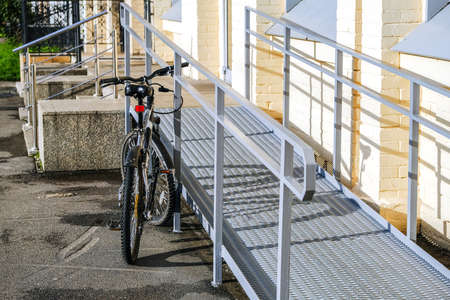 A ramp for wheelchairs. The bike is in the foreground, attached to the railing with an anti-theft cable and locked