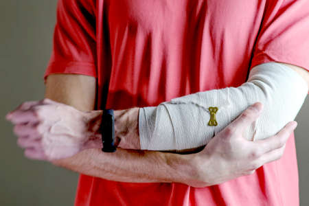 The man supports the injured hand. Primary care, the hand is tightly fixed with an elastic bandage 版權商用圖片