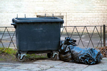 Garbage container on wheels. A plastic trash bag is thrown nearby. Concept of a commercial cleaning company