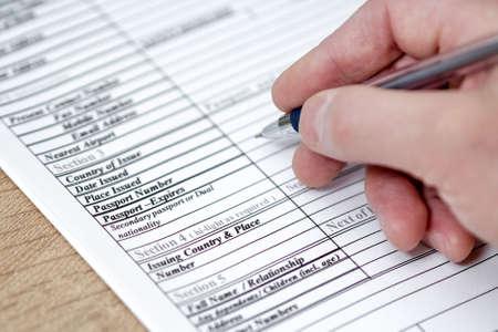 Filling in an application form for visa entry. Banque d'images