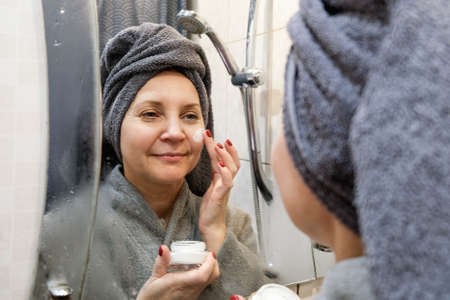 A young woman in the bathroom, right after taking a shower, with a towel wrapped around her head. Applying the cream to the face