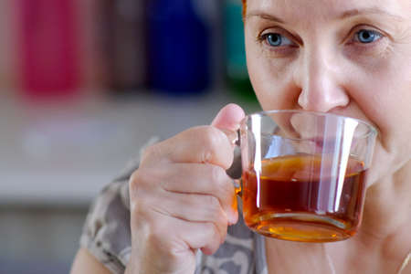 Attractive woman drinking tea. In thought, the gaze is directed somewhere in the distance