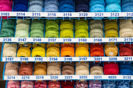 Atelier workshop. A set of colored threads for sewing on reels. A bunch of large multicolored spools of thread