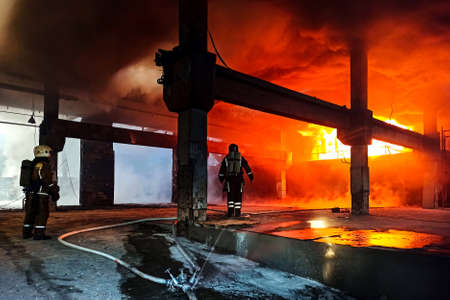 Firefighters in heat-resistant suits near an open fire. A thick layer of smoke. Behind the back of oxygen tanks On the head of protective helmets. The concept of protecting and saving the city's population