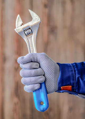 The master holds in his hand an adjustable locksmith key with a blue handle. Locksmith repair work.