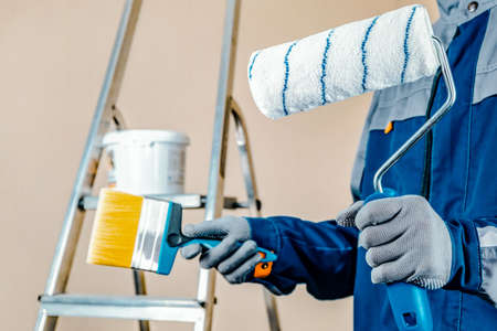 The plaster painter is ready to paint the wall. In the hands of a roller and brush. A stepladder and a bucket of paint in the background.