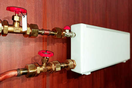 Red thermostat accessory. Plumbing services. copper pipe of the heating system in the boiler room