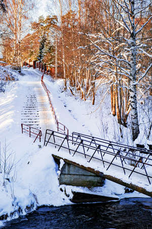 A bridge over a small river. A majestic winter landscape, shining with sunlight in the morning. Dramatic winter scenes.