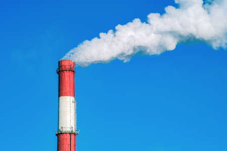 Industrial pipe on a blue sky background. It throws clouds of smoke into the sky. Air pollution by dioxide. Environmental pollution.
