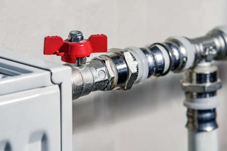 Red thermostat accessory. Plumbing services. Chrome-plated heating system pipe connectors.