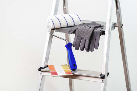 Everything for painting, roller, gloves and sheet for choosing shades. A stepladder in the background. 版權商用圖片