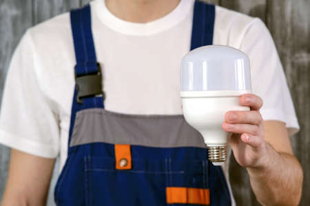 An electrician in a blue jumpsuit. In his hand, he holds a powerful industrial energy-saving light bulb. Concept of energy saving. 版權商用圖片