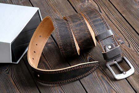 The belt is rolled up, next to a gift box. Template for the design of leather accessories. Background, shiny metal belt buckle. Abstract background. Texture background.