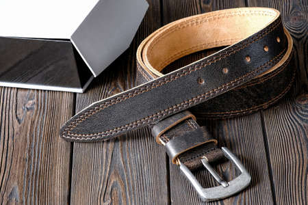 The belt is made of cowhide genuine leather, next to a gift box. Template for the design of leather accessories. Background, shiny metal belt buckle. Abstract background. Texture background. Banco de Imagens