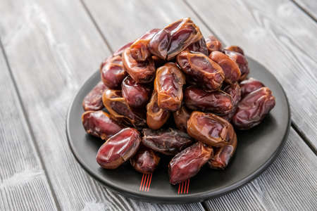 Close-up of red raw organic dates, a pile on a saucer. Healthy eating. Organic food. Delicious food. The natural background. Banco de Imagens