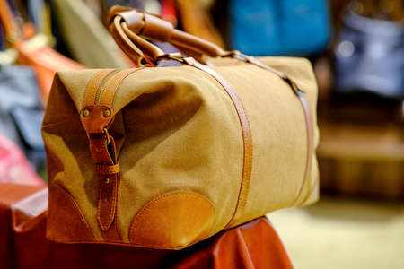 Travel bag made of tarpaulin with leather inserts. The concept of stylish leather products. Bags, purses and belts.