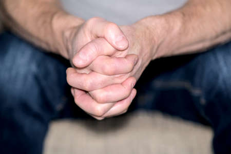 A mans intertwined fingers, a close-up of his hands folded in thought.