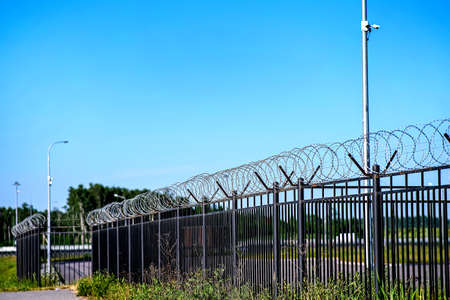 The restricted area is fenced with a fence with barbed wire. A fence around a restricted area with CCTV cameras on poles