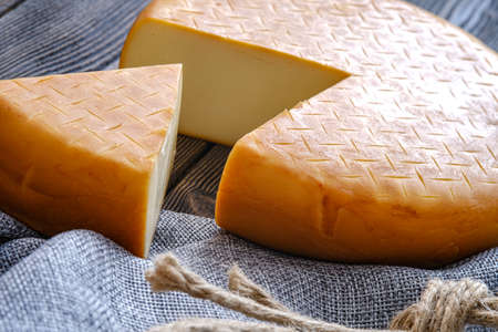 A head of ripened Georgian suluguni cheese, with a cut-out piece for a conceptual design. The concept of nutrition.