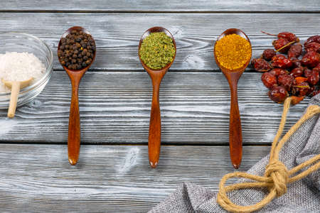 Spoons of various spices on a rustic wooden table. Top view. The concept of cooking delicious dishes.