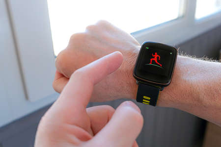 Man adjusting settings of sports watch for outdoor training Banco de Imagens
