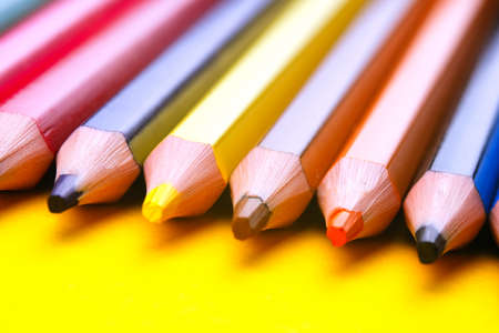 Background, blur, out of focus, bokeh. Colored pencils isolated on a yellow background. The concept of creativity development.
