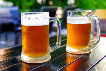 Glasses of light beer with barley on the background of an open street pub