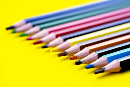 Colored pencils isolated on a yellow background. The concept of creativity development.