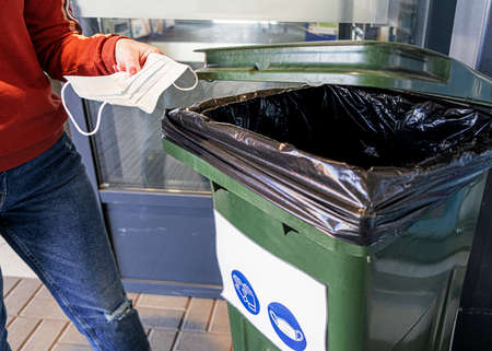 The girl throws the protective medical mask in the trash. A woman holds a used medical mask in her hand. Banco de Imagens