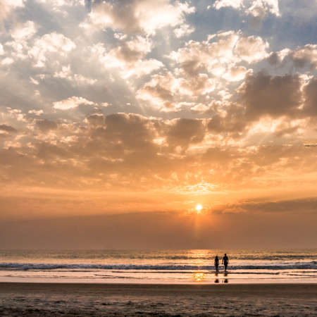 honey moon: Lovely couple going to the ocean on the sunset in Goa, India Stock Photo