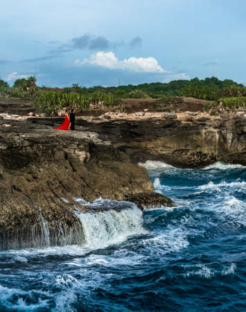 raging: Romantic couple standing on the cliff above the raging sea Stock Photo