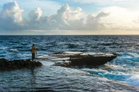 breaking waves: Young man standing in front of raging sea and breaking waves