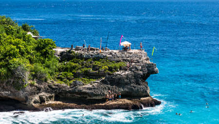 cliff jumping: Cliff jumping area. People jumping to the water and relaxing on the beach