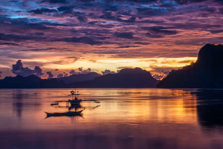 nido: Tropical colorful sunset with a banca boat in El Nido, Palawan Stock Photo