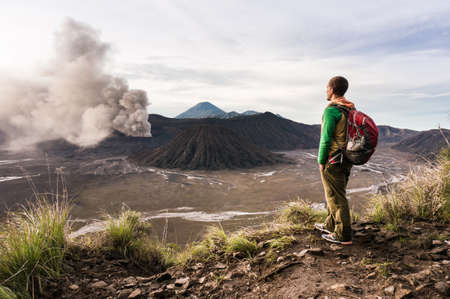 Man on the hill is looking on Bromo volcano eruption