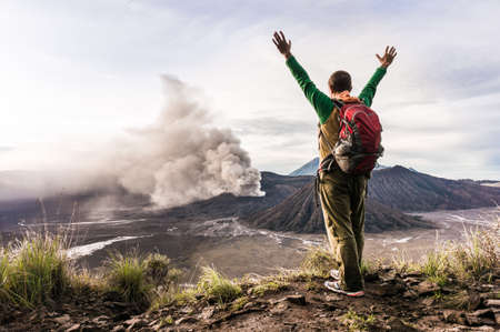 achievment: Encouraged man on the hill is looking on Bromo volcano eruption Stock Photo