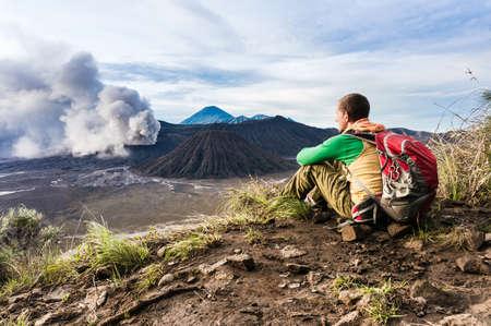 achievment: Man is sitting on the hill and looking on Bromo volcano eruption