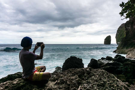 overwhelming: Young man sitting on the rock and making a photo of the waves Stock Photo