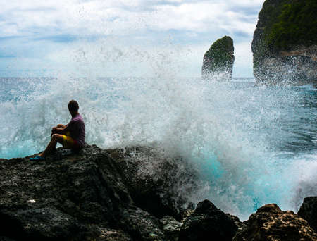 breaking in: Young man sitting on the rock with the sea waves breaking in front