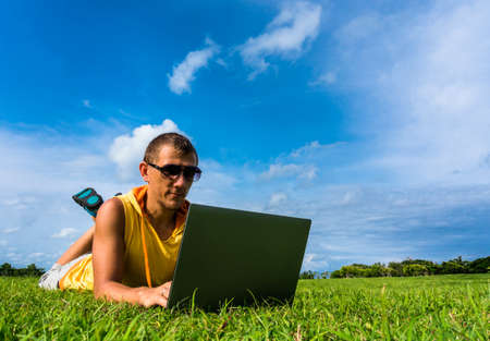 25 30: Young man lying on the grass and working with laptop