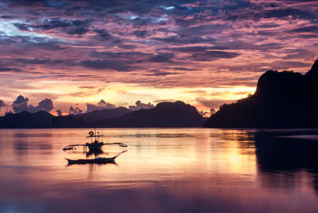 nido: Tropical colorful sunset with a banca boat in El Nido, Palawan, Philippines Stock Photo