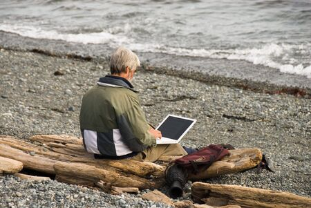 A man works on his laptop at the beach.