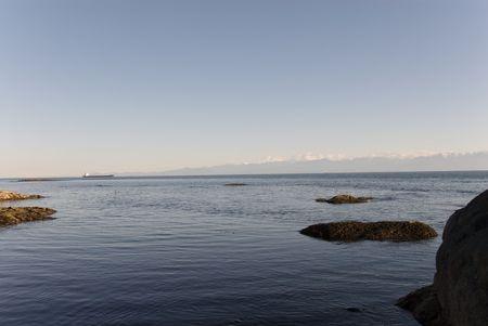 strait of juan de fuca: A distant ship plies the Strait of Juan de Fuca