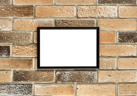 A photo frame with white empty space for text hangs on an old brick wall. Grunge brick wall with a photoframe hanging on it