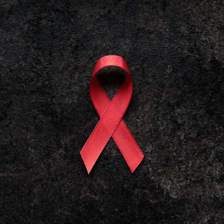 AIDS awareness red ribbon on a dark background