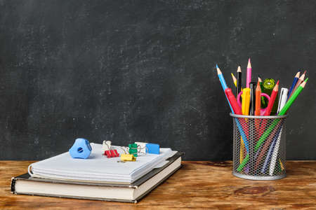 School supplies such as textbook, notebook, pens, pencils, scissors and other over chalkboard background