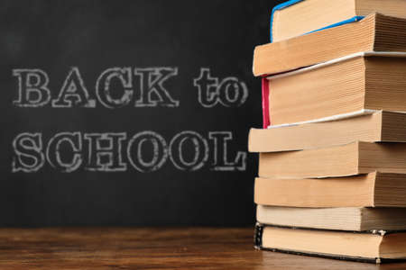 Back to School. Education concept with stack of books on a wooden school desk against the background of the blackboard
